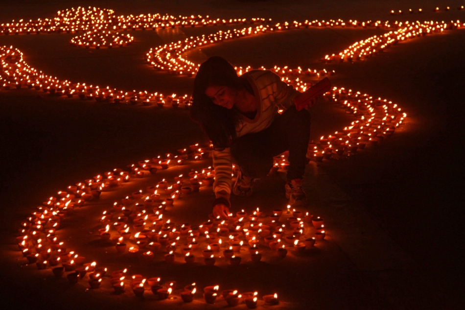 A girl lights earthen lamps in a formation to make the shape of Hindu god Ganesh on the eve of Diwali in Chandigarh
